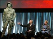 "Outgoing National Rifle Assn. president Charlton Heston gestures toward a statue of the character he played in the movie ""Will Penny"" with his wife, Lydia, at his side in Orlando, Fla. The statue was presented to Heston on Friday at an NRA tribute in his honor; Saturday, he made he last appearance as NRA president."
