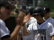 Free State's Ryne Price (11) is congratulated after he crosses the plate for one of the two runs he scored in the Firebirds' 8-7, nine-inning victory over Lawrence High. FSHS won the city showdown Saturday at Free State.