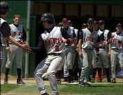 Lawrence High catcher Tommy Mangino is congratulated by teammates after he belted a two-run home run. The Lions lost an 8-7 decision to Free State in nine innings Saturday at Free State Field.
