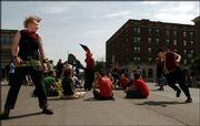 "Anarchists and peace demonstrators pass the time with a game of badminton and ""anarchist, anarchist, goose,"" a takeoff on ""duck, duck, goose,"" during a sit-in near the intersection of Seventh and Massachusetts streets. The group of protesters Saturday marched the length of Massachusetts Street, from 23rd Street to Sixth Street."