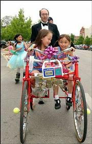 "With a modified bicycle called ""Four-Wheel Wonder,"" Jeff Moran pushes his daughters Hannah, left, 7, and Rebecca, 5, down New Hampshire Street. The sisters rode in style at the Art Tougeau parade Saturday in downtown Lawrence."