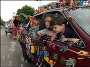 "Layla Wilson, left, 10, and Benjamin Slimmer, 3, peek out of the ""Toy Car"" mobile. From dolled-up pets to modified cars and cycles, the Art Tougeau parade proceeded to a wild and wacky drumbeat Saturday in downtown Lawrence. The toy-covered car entered by Pat Slimmer, of Lawrence, took first place in the parade."