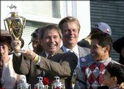 Owner Jackson Knowlton holds up the trophy in the winner's circle after his horse, Funny Cide, won the Kentucky Derby. Owner David Mahan, center, and jockey Jose Santos, right, also bask in the celebration Saturday in Louisville, Ky.