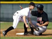 Free State high's Robby Price, left, is late with the tag as Shawnee Mission Northwest's Greg Rawlings steals second. Northwest won, 4-3, Tuesday at FSHS.