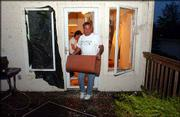 Dave Hurtig carries out belongings from the damaged home of his friends George and Tonia Waters. The Waterses' home on Rodeo Drive in the southwest part of Lawrence was damaged Thursday evening when a tornado ravaged the area.