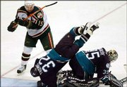 Anaheim's Steve Thomas (32) flies over goalie Jean-Sebastien Giguere after defending against a scoring attempt by Minnesota's Andrew Brunette in the third period. The Ducks dumped the Wild, 1-0 in double overtime, Saturday in St. Paul, Minn.