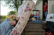 Anithia Miller, 5, plays on a mattress propped against the porch as her mother, Annette, watches Sabrina. The Millers purchased the trailer near the Douglas County 4-H Fairgrounds for $200 after living through winter in a rented trailer heated by a oven. The girls played Monday outside their home.