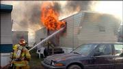 Lawrence firefighters respond to a fire at the trailer home of David Sears and Anita Owens in this Dec. 31, 2002, file photo. Sears and Owens blamed the fire on faulty electrical wiring; their landlord, JoAnn Qandil, blamed space heaters.