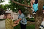 When Danette Seymour felt burned by her landlord, she organized the Kansas Tenants Union. Today, she helps renters when they have disputes with their landlords. Last week, she played with her sons, Jordan, left, and Caleb, in tree, in front of their west Lawrence duplex.