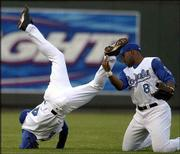 Kansas City shortstop Angel Berroa, left, is tossed in the air as he collides with left fielder Dee Brown. The Royals were upended by the Blue Jays, 7-4, Saturday in Kansas City, Mo.