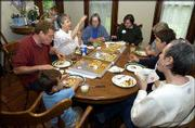 Members of Delaware Street Commons conduct a meeting over pizza. They met Friday at the McMillan House, 1208 Del.