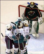 Minnesota Wild goalkeeper Manny Fernandez, right, hangs his head as Anaheim players congratulate Adam Oates (77) after he scored a goal. The Mighty Ducks beat the Wild, 2-1, Friday in Anaheim, Calif., to advance to the Stanley Cup finals.