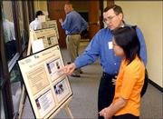 Robert Isaacson, left, and Thanawan Phongsatha, both with the Center for Research on Learning at Kansas University, talk about one of the posters during KU's Information and Telecommunication Technology Center's Technology Day. During the Technology Day celebration Monday, Sprint Corp. and KU announced that their 10-year partnership had produced a third patented discovery.