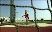 Nebraska's Becky Breisch, seen through the netting around the discus ring, warms up before her event. Breisch won Monday at Austin, Texas, at the Big 12 Conference Outdoor Track and Field Championships with a throw of 180-10.