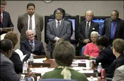 Singer James Brown, standing center, appears before the Department of Probation, Parole and Pardon Services board in Columbia, S.C. The seven-member board on Tuesday granted Brown a pardon for crimes he committed in 1988 and 1998.