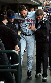 Mets catcher Mike Piazza is helped to the clubhouse after he tore his right groin Friday. Piazza will miss at least six weeks and possibly the rest of the season after the incident in San Francisco.