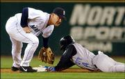 Seattle second baseman Bret Boone reaches to tag Kansas City's Angel Berroa at second base in the third inning. Berroa, who was hit by a pitch earlier in the inning, was safe with a stolen base. The Royals lost to the Mariners, 7-4, Tuesday at Safeco Field in Seattle.
