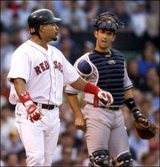 New York Yankees catcher Jorge Posada, right, escorts Boston's Manny Ramirez to first base after Ramirez was hit by a pitch. The Red Sox beat the Yankees, 10-7, Tuesday in Boston.