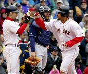 BOSTON'S NOMAR GARCIAPARRA, left, greets teammate Manny Ramirez, right, as Cleveland catcher Josh Bard looks on. Ramirez hit a two-run home run in the seventh inning of Boston's 12-3 victory over the Indians Saturday in Boston.