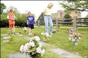 Tyler Kring, 13, left, his brother Connor Kring, 11, and their mother, Kirsten Price, all of Lawrence, walk through Pioneer Cemetery on Kansas University's West Campus.