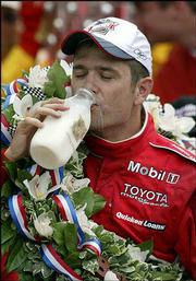 Gil de Ferran drinks the traditional bottle of milk after his victory Sunday in the Indianapolis 500 at Indianapolis Motor Speedway.