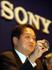 Ken Kutaragi, Sony's executive deputy president, holds a new MD disk during a press conference in Tokyo. Sony Corp. on Wednesday touted its revamped Playstation 2 videogame machine that also has a DVD recorder and TV tuner, which will be able to download movies and music using the disk.