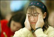JJ Goldstein, 13, of Great Neck, N.Y., rubs her temples while taking the written test during the second round of the 76th annual National Spelling Bee in Washington. The finals of the bee will be televised today.