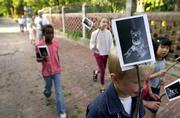 Rich Brown, 8, helps lead a parade around the 700 block of Indiana and Louisiana streets, holding a photograph of Sam, a 15-year-old schnauzer who died in December. The New Orleans-style wake in honor of the pet Saturday kicked off the neighborhood's block party.