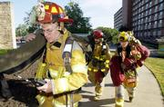 Capt. James Sloan, foreground, leads Lt. Marshall Biggerstaff, center, and firefighter Melissa Warren into McCollum Hall at Kansas University. The firefighters, from Fire Station 4, took part in a training exercise Friday at the residence hall.