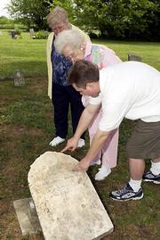 During their 90th family reunion, members of the Hoover family look at the grave marker of Isaac B. Hoover in Colyer Cemetery southeast of Lone Star. Pictured are, from left, Mary Kamp, of Richardson, Texas, her mother Gulah Hoover Daron, Oklahoma City, and Kamp's son, Michael Kamp, Richardson, Texas. Isaac Hoover, who died in 1866, was Daron's great-grandfather.