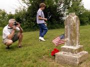 Larry Saathoff, Lawrence, photographs a grave marker as his aunt Patty Hoover, Queen City, Mo., walks by in the Colyer Cemetery southeast of Lone Star Lake. Members of the Hoover family visited cemeteries on Saturday during their 90th family reunion.