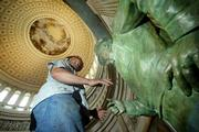 Migal Despanza removes straps from the statue of Dwight D. Eisenhower after it was lowered into place in the U.S. Capitol Rotunda in Washington. The Eisenhower statue, by Lawrence, Kan., sculptor Jim Brothers, arrived Saturday.