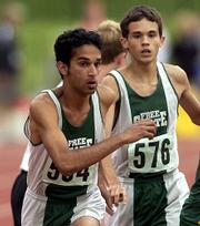 Free State High's Hiral Bhakta, left, takes the baton from Danny Schneider. The Firebirds won the 4x800 relay Saturday at the Class 6A state meet in Wichita.