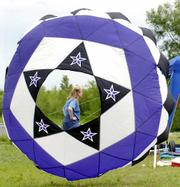 """Susie Gilson, Olathe, is framed by her bowl-shaped """"bol"""" kite, which she made herself. Gilson&squot;s kite is tethered to a pole."""