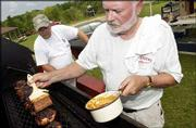 """John Thomann, left, and Jim Powers, both of Lenexa, prepare chicken before the judging at the 12th annual BBQ Blowout in McLouth. The """"Bum Steers"""" were at Prairie Park on Saturday for the cookoff."""
