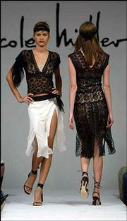 A black V-neck lace top with asymmetric mesh handkerchief pieces is modeled over a white georgette panel skirt with black yoke during the showing of the Nicole Miller Spring 2003 collection in New York. At right is a black lace strip dress with nude slip. The slinkier look of the bedroom is increasingly becoming part of everyday street fashion.
