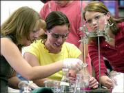 Ione High School juniors, from left, Meghan McCabe, Natalie McElligott and Emily Key work on a science experiment during class in Ione, Ore. In an effort to keep the small town's high school from being shut down and its students bused 20 miles away, Ione residents persuaded the Oregon Legislature to create their own school district.