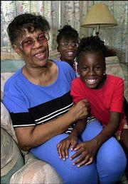 Edna Myles 61, poses with granddaughters Patrice, center, and Ericka. Freddie and Edna Myles have taken in five of their grandchildren who otherwise would have gone to foster homes because they were neglected or abandoned by their own parents. The Florida Kinship Center at the University of South Florida helps them with the challenges of child-rearing.
