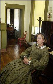 The Independence, Mo., museum features period furniture, including this desk and chair. Costumed interpreters, including Church, above, guide museum visitors and answer questions.