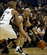 New Jersey's Jason Kidd, right, works the ball around San Antonio's Tony Parker. Kidd helped the Nets defeat the Spurs, 87-85, Friday night in San Antonio. The series is tied at one game apiece heading into tonight's game in East Rutherford, N.J.