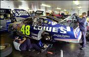 Crew members work on Jimmie Johnson's race car in the garage area of the Pocono Raceway. Heavy rains forced officials to cancel the morning practice session Saturday for today's Pocono 500 in Long Pond, Pa.