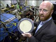 Daniel Ricoult, a business technology director at Corning, holds a diesel particulate filter that is to be attached to the exhaust of a diesel truck engine for testing in Corning, N.Y. Within five years, every new diesel vehicle will need to be equipped with filters and catalysts that trap soot and convert lung-choking gases into carbon dioxide, nitrogen and water vapor. Corning revealed the filter on Jan. 2, 2002.