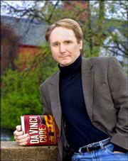 "Author Dan Brown poses in his hometown of Exeter, N.H., prior to a reading from his new book ""The Da Vinci Code."" The volumn, Brown&squot;s fourth novel, is a mixture of code-breaking, art history, secret societies, religion and lore, all wrapped up in a fast-paced thriller."
