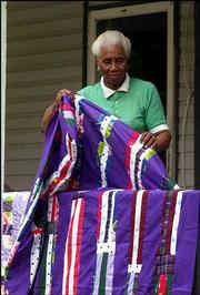 Arlonzia Pettway folds one her many quilts on the porch of her Gee's Bend, Ala., home. Pettway quilts with a group of local black women who recently gained international recognition for their quilt exhibition at the Whitney Museum in New York.