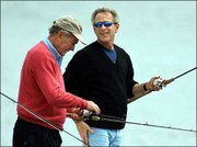 President Bush, right, chats with his father, former President Bush, as the two fish together off the coast of Kennebunk, Maine.