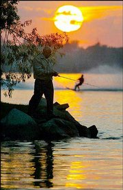 Isaac Pann, a 77-year-old fisherman from West Bloomfield, Mich., is silhouetted by the setting sun as he fishes on Orchard Lake, Mich. A waterskier passes in the background.