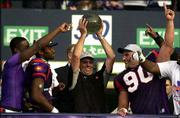 Frankfurt Galaxy coach Doug Graber, center, holds the championship trophy as he celebrates with his players. The Galaxy routed the Rhein Fire, 35-16, in the NFL Europe World Bowl Saturday at Hampden Park Stadium in Glasgow, Scotland.