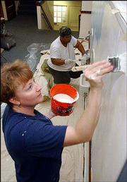 Rebecca Lyles, foreground, and Christie Yancy paint a hallway at Cordley School, 1837 Vt. Tests of flaking paint at the school show that students may have been exposed to lead, which can cause health problems in children. Lead paint is present in many structures built before 1978, the year it was banned.