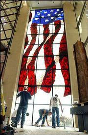 Workmen for Stained Glass Overlay, of Roseville, Minn., place the final panes of a stained-glass American flag, believed to be the largest in the world, in the Dole Institute of Politics at Kansas University. The 36-foot-high, 1-ton window was completed Tuesday.