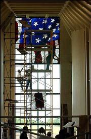 Workers for stained glass overlay, of Roseville, Minn., climb a scaffold at the Dole Institute of Politics at Kansas University to install panels of glass that create a 36-foot-high American flag. Installation of the window was completed Tuesday.